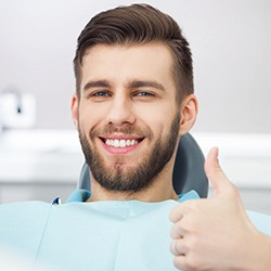 man in the dental chair giving a thumbs-up