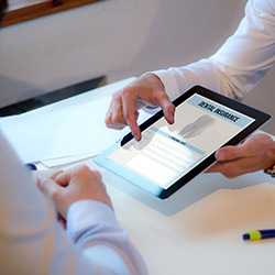 dentist showing a tablet with insurance paperwork on it to a patient