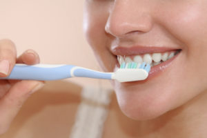 woman brushing his teeth smiling