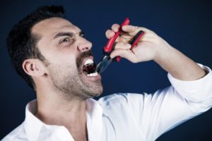 bearded man pulling tooth pliers