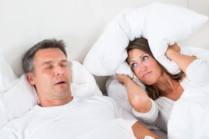 a man asleep and snoring and a woman covering her ears with a pillow